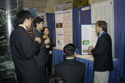 Justin Kovac explaining his research to 4 others.