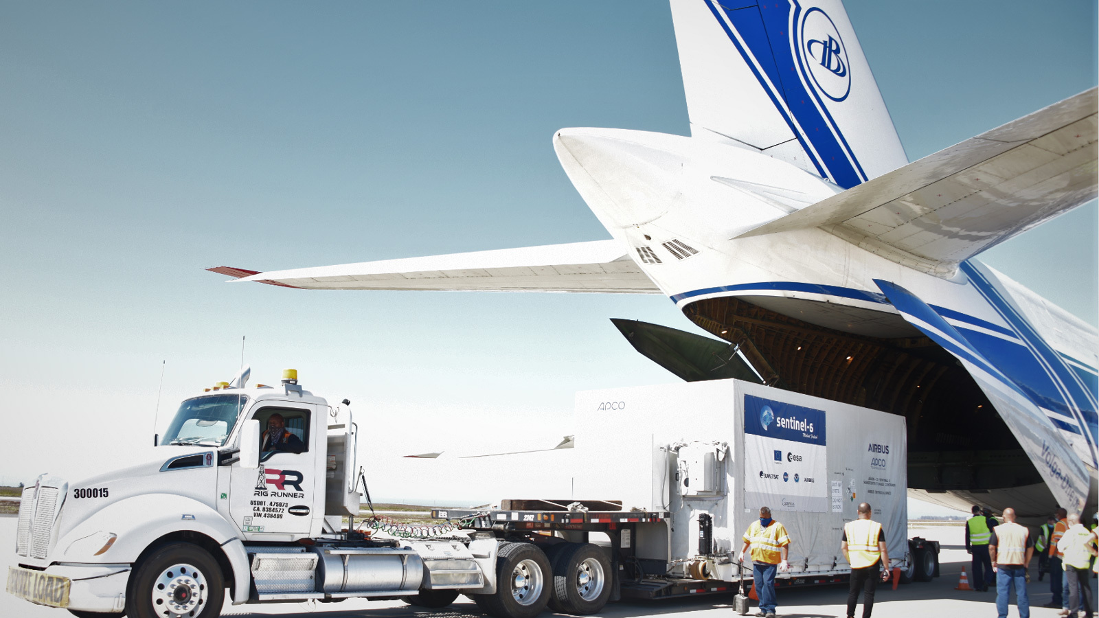 A photo of the spacecraft container being unloaded from a plane.